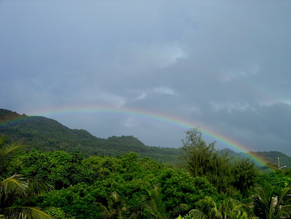 A rainbow graces the jungle foliage of the Guam mountains.