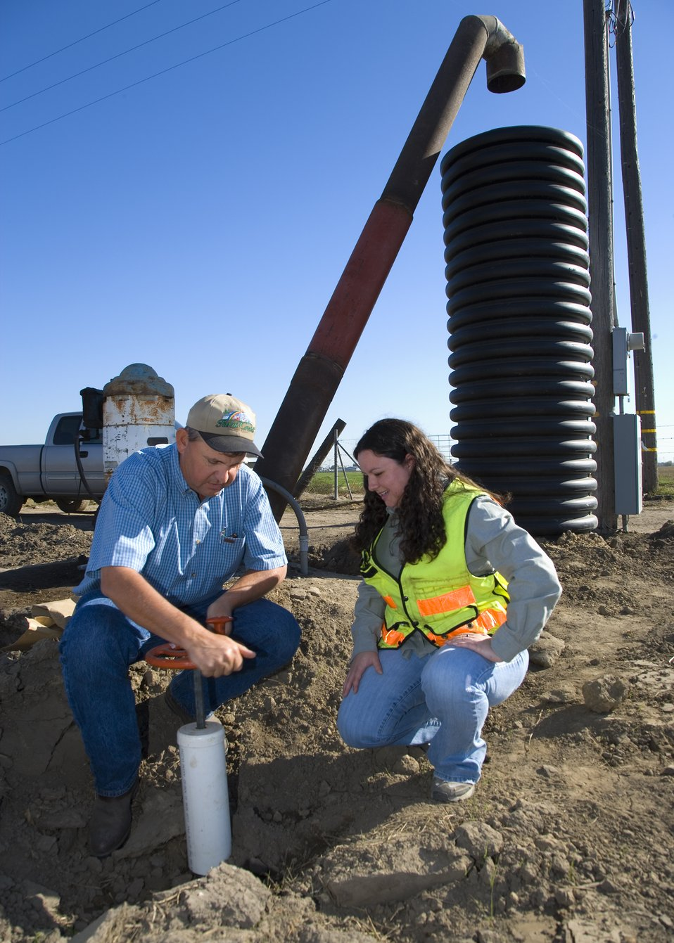 NRCS and farmer inspecting stand pipe on a dairy farm in California.