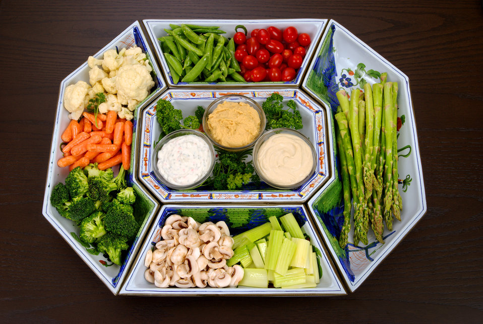 This vegetable platter includes some very healthy ingredients including snow peas, cherry tomatoes, asparagus, celery, mushrooms, broccoli,