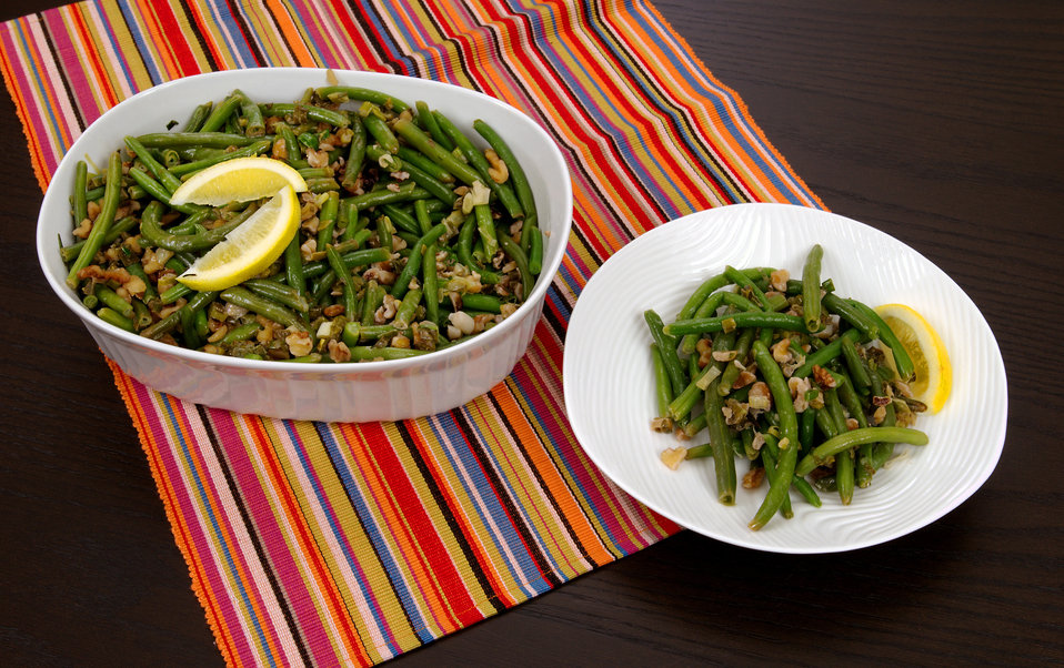 This image depicts a casserole dish filled with a freshly-cooked recipe of Lemon-Walnut Green Beans, which based on its ingredients, is a ve