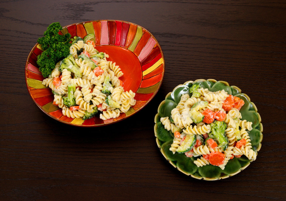 This image depicts a plate of Pasta Primavera, from which a single serving had been removed, and plated on its own small serving dish.