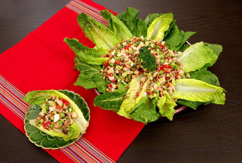 This image depicts a delicious-looking black-eyed bean salad set atop a circle of romaine lettuce leaves. The salad included green and red p