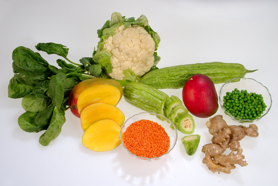 This image depicts a grouping of healthy fruits and vegetables, including a head of cauliflower, a bunch of spinach, a mango, bitter melon,