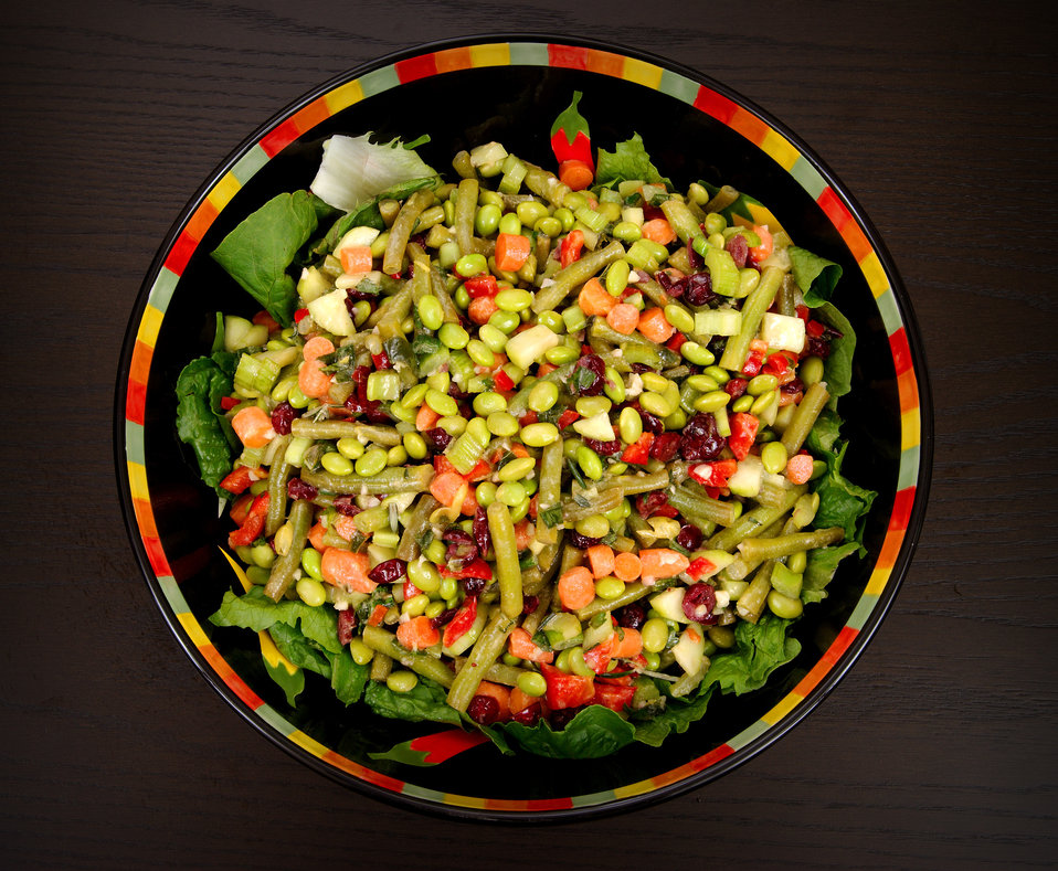 This photograph depicts a bowl filled with a freshly-prepared side dish of Marinated Edamame Salad. Built around the vitamin C-rich, fiber p