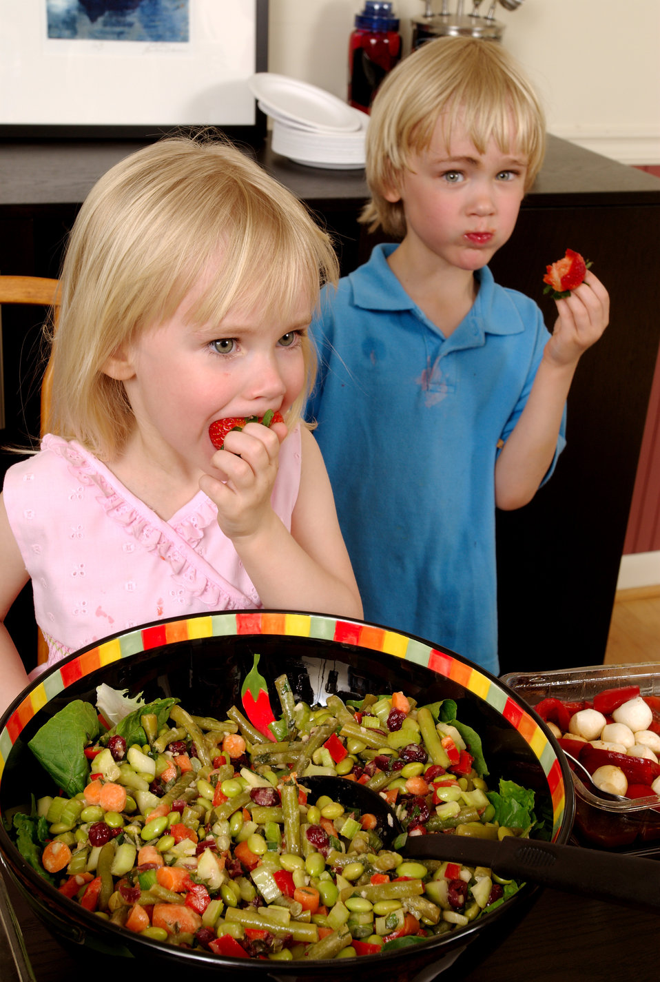 Here, two young children were at a dining table, upon which was plated a large quantity of foods representing a number of different food gro