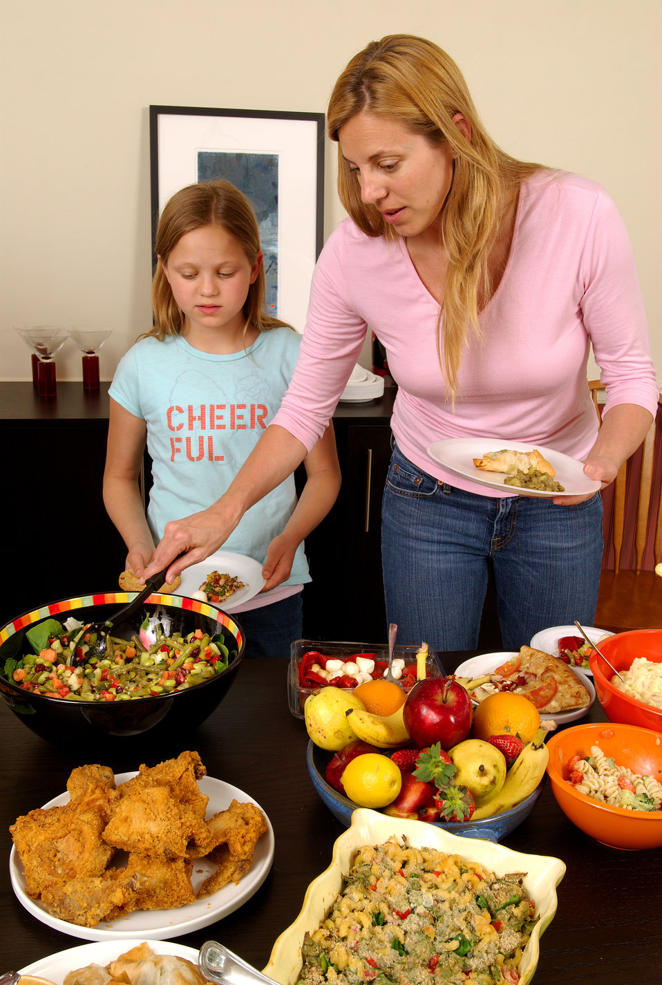 This image depicts a young girl and her mother, serving themselves at a dining table, atop which was plated a large quantity of foods repres