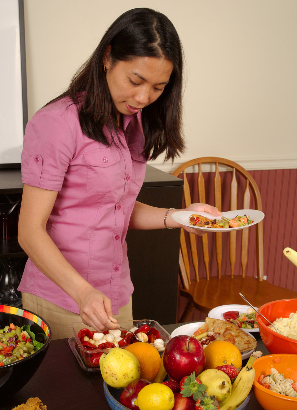 This image depicts a young woman serving herself from a dining table, atop which was plated a large quantity of foods representing a number