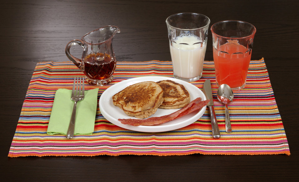 Here we see a simple breakfast including a glass of low-fat milk, a glass of grapefruit juice, what appears to be two, small whole wheat pan