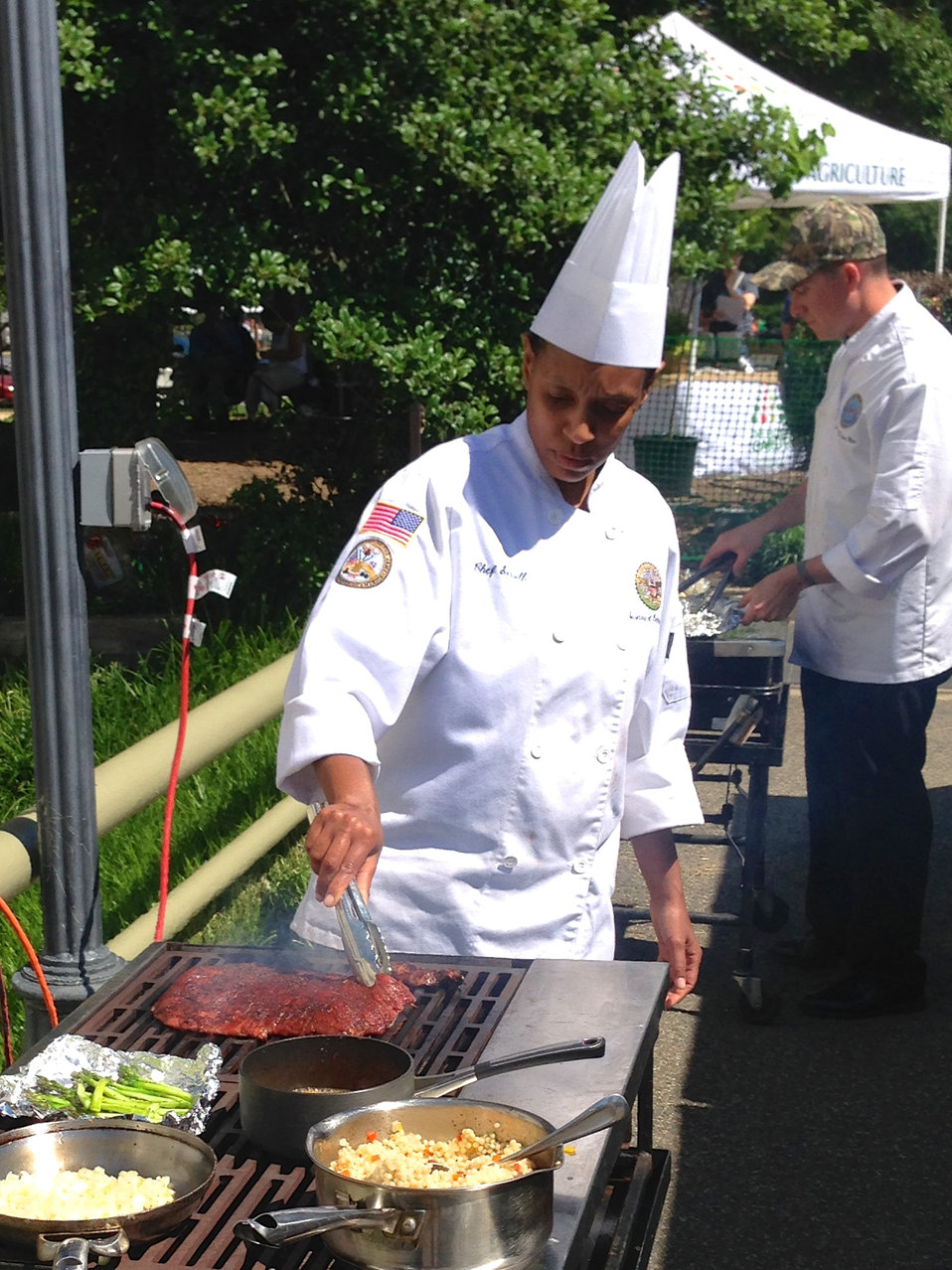 Winner of the BBQ Battle Chef and Army Sergeant Monica Sorrell works the grill during the competition