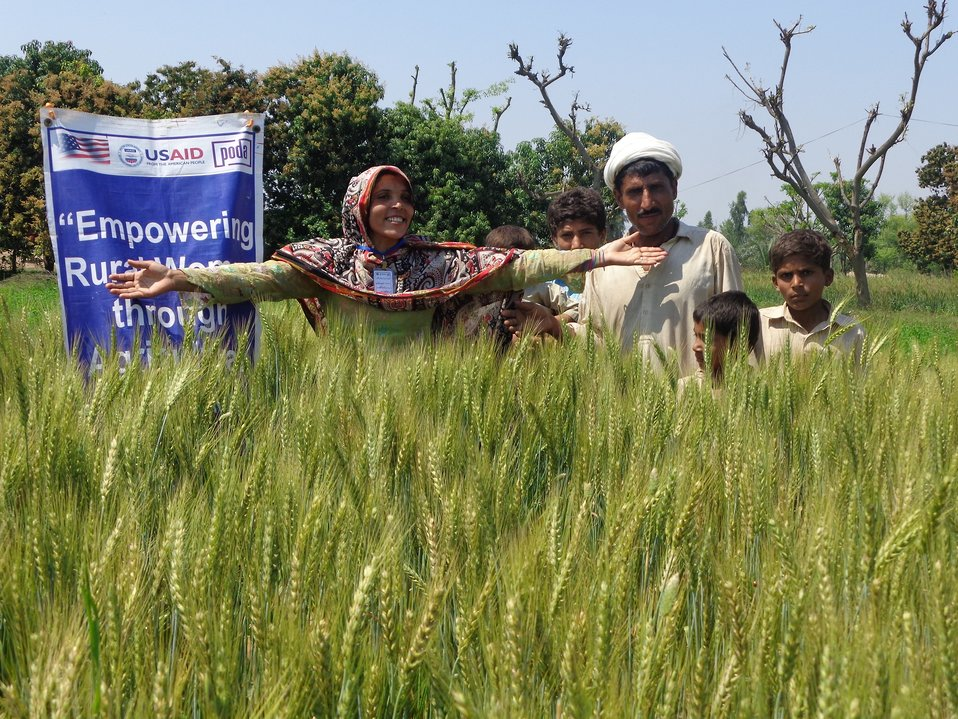 Ms. Nuzhat Bibi (Project Beneficiary) with her family in her wheat field-PODA MZG