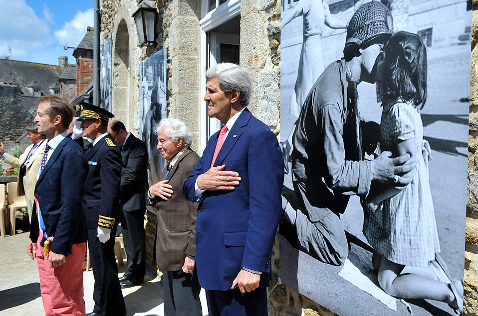 Secretary Kerry, Photographer Vaccaro Pause For National Anthems in Saint Briac