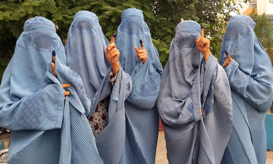 Women show inked fingers after voting in Herat. Afghan law requires a voter to dip his or her finger in indelible ink before receiving a ballot, to help prevent election fraud. A voter's fingers must be ink-free, in order to receive a ballot.