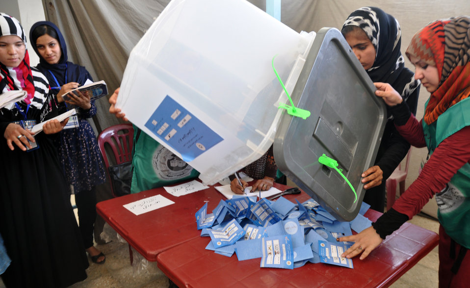 IEC workers open ballot box for counting ballots in Kabul.