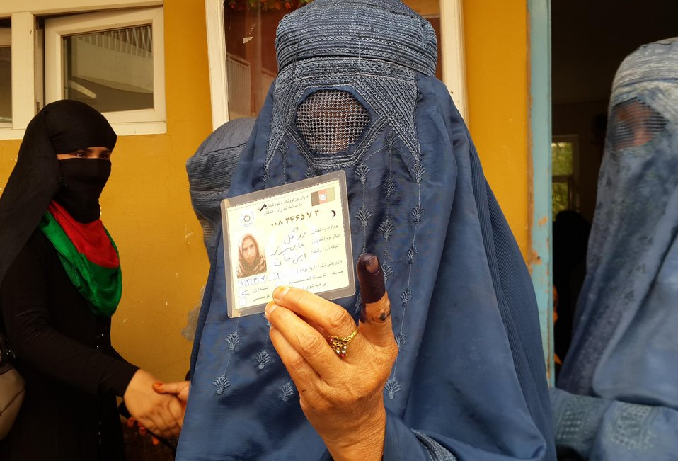 A burqa-clad woman shows her inked finger and voting card after casting her vote in Afghanistan's northern Kunduz province.