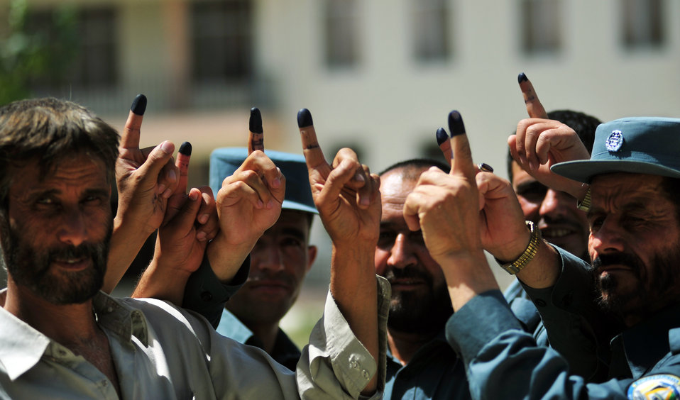 Voters after casting their votes show their inked finger to journalists in Kabul.