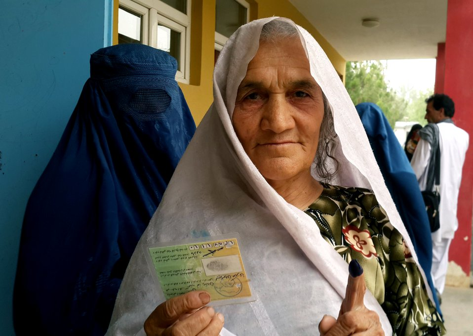 An Afghan woman shows her inked finger and voting card after casting her vote in Kunduz province.