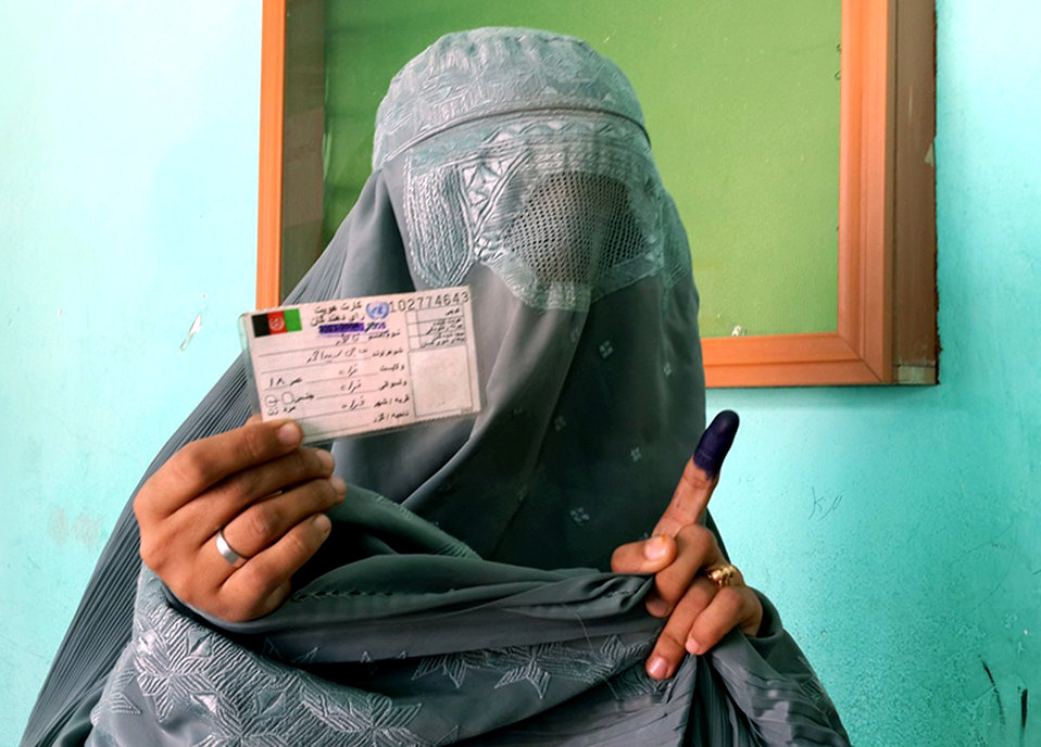 A woman after casting her vote shows her finger and voting card to media-people in Farah province.
