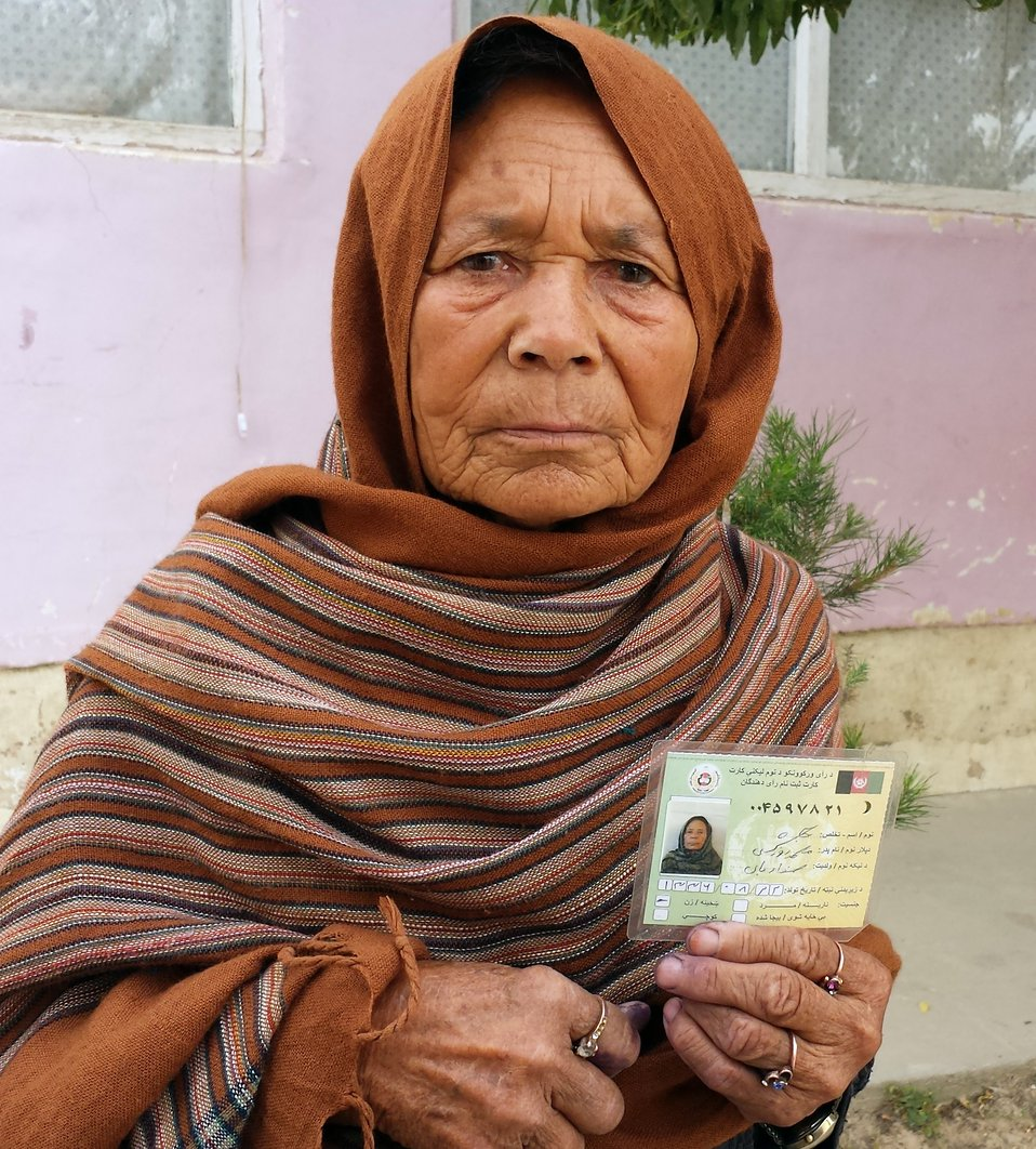 A woman displays her voting card in Samangan province.
