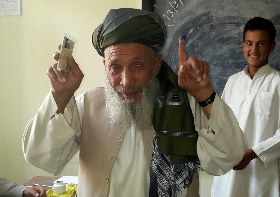 A man shows his inked finger and voting card after casting his vote in Afghanistan's northern Panjshir province.