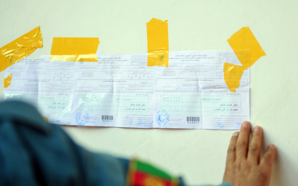 A policeman hangs result list of a polling center in Kabul.
