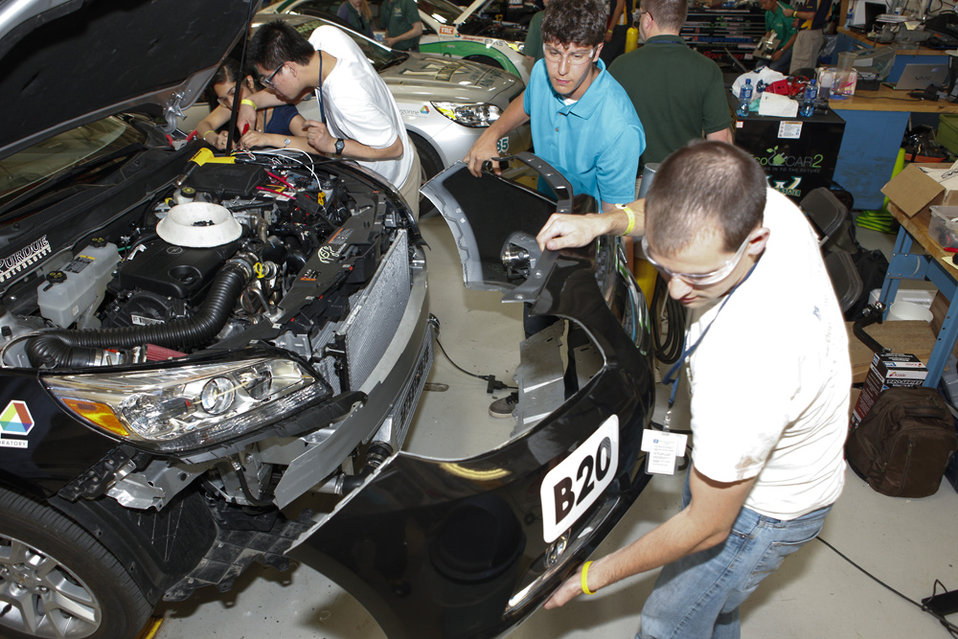 Students from Purdue University work on their vehicle, making last-minute adjustments before a day of tests. The team's vehicle can run