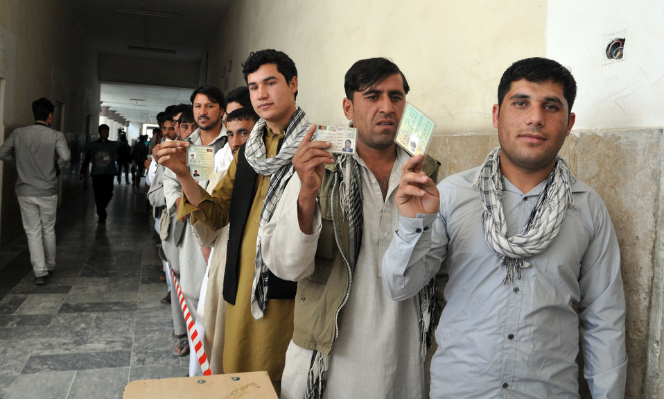 Afghan men display voting cards in front of a Kabul polling center.