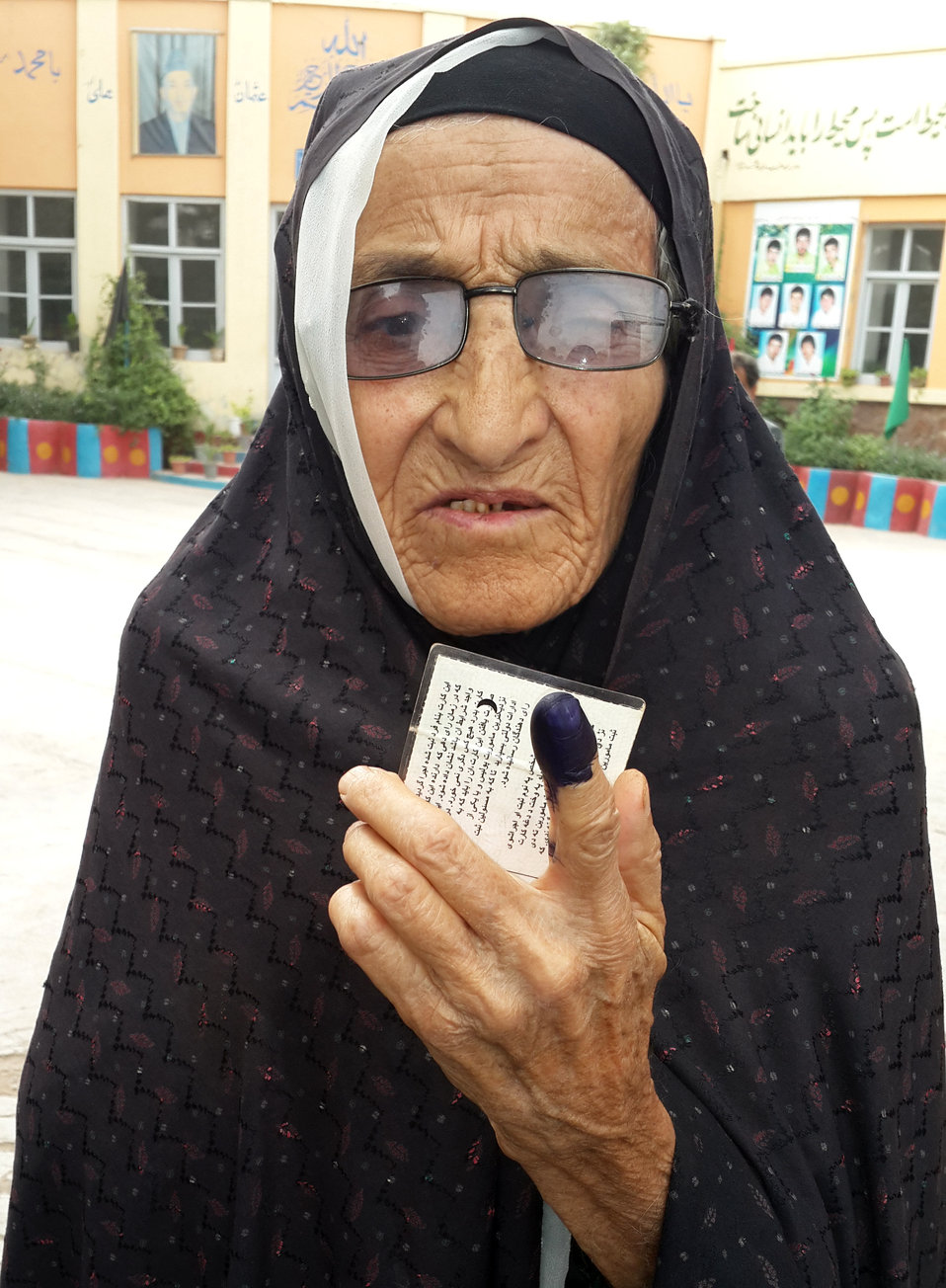 An elderly woman shows her coloured finger after casting her ballot in Herat.