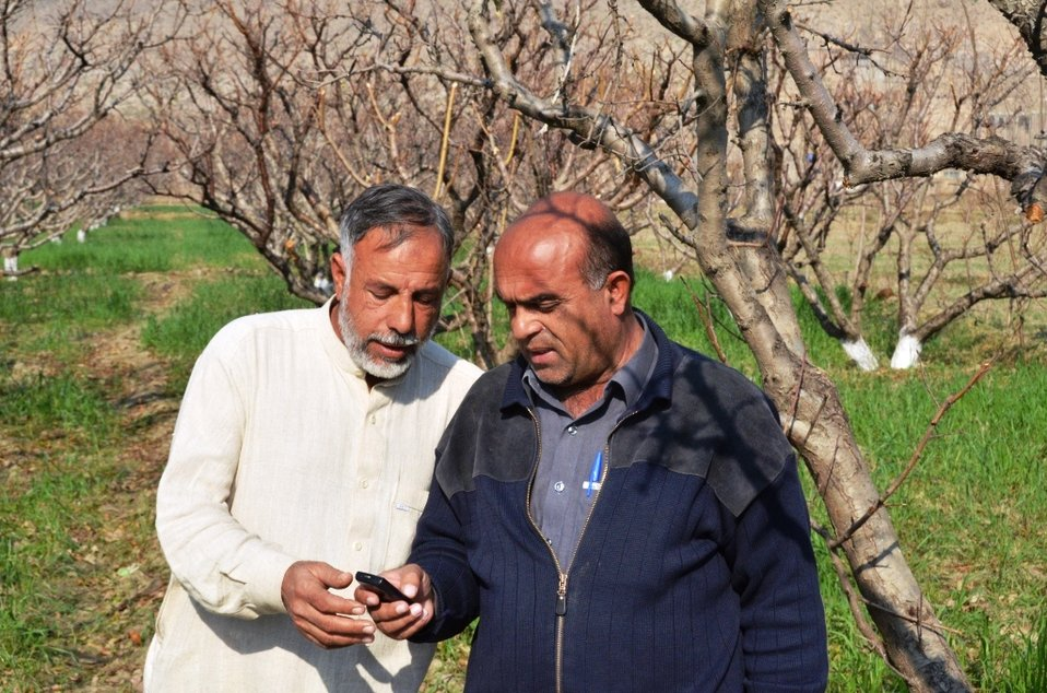 A subscribed farmer is sharing information with a non-subscribed farmer in his community.