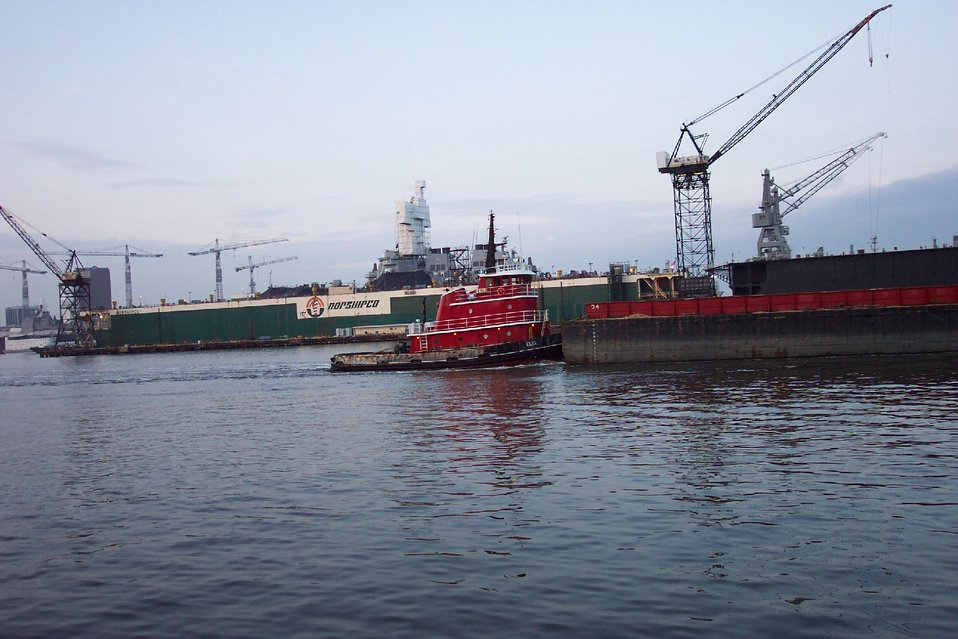 Tug pushing barge down the Elizabeth River with Navy ship in drydock.