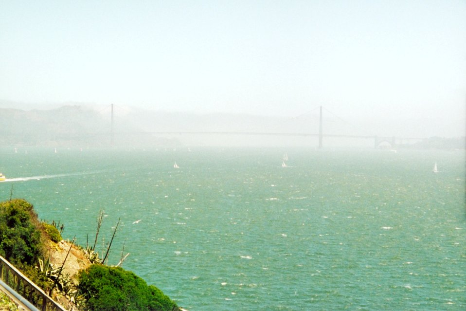 The Golden Gate Bridge on a hazy foggy afternoon.  Sailboats in the distance are  dwarfed by the bridge.