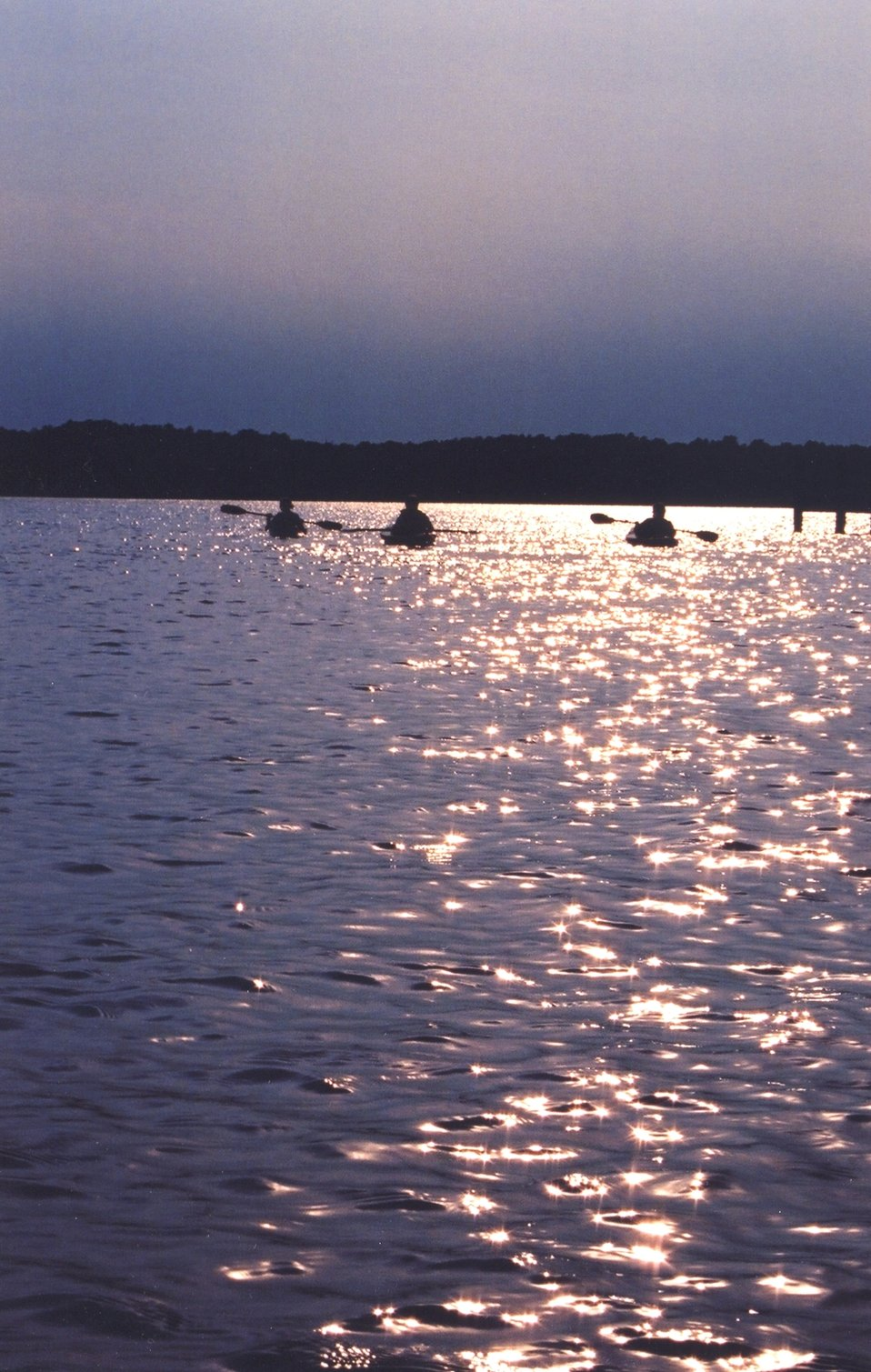 Late afternoon sun-glint on the lower Patuxent River silhouetting a group of kayakers.