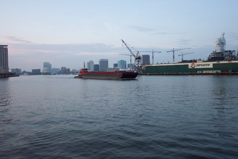 Tug pushing barge down the Elizabeth River with Norfolk skyline and shipyard in picture.