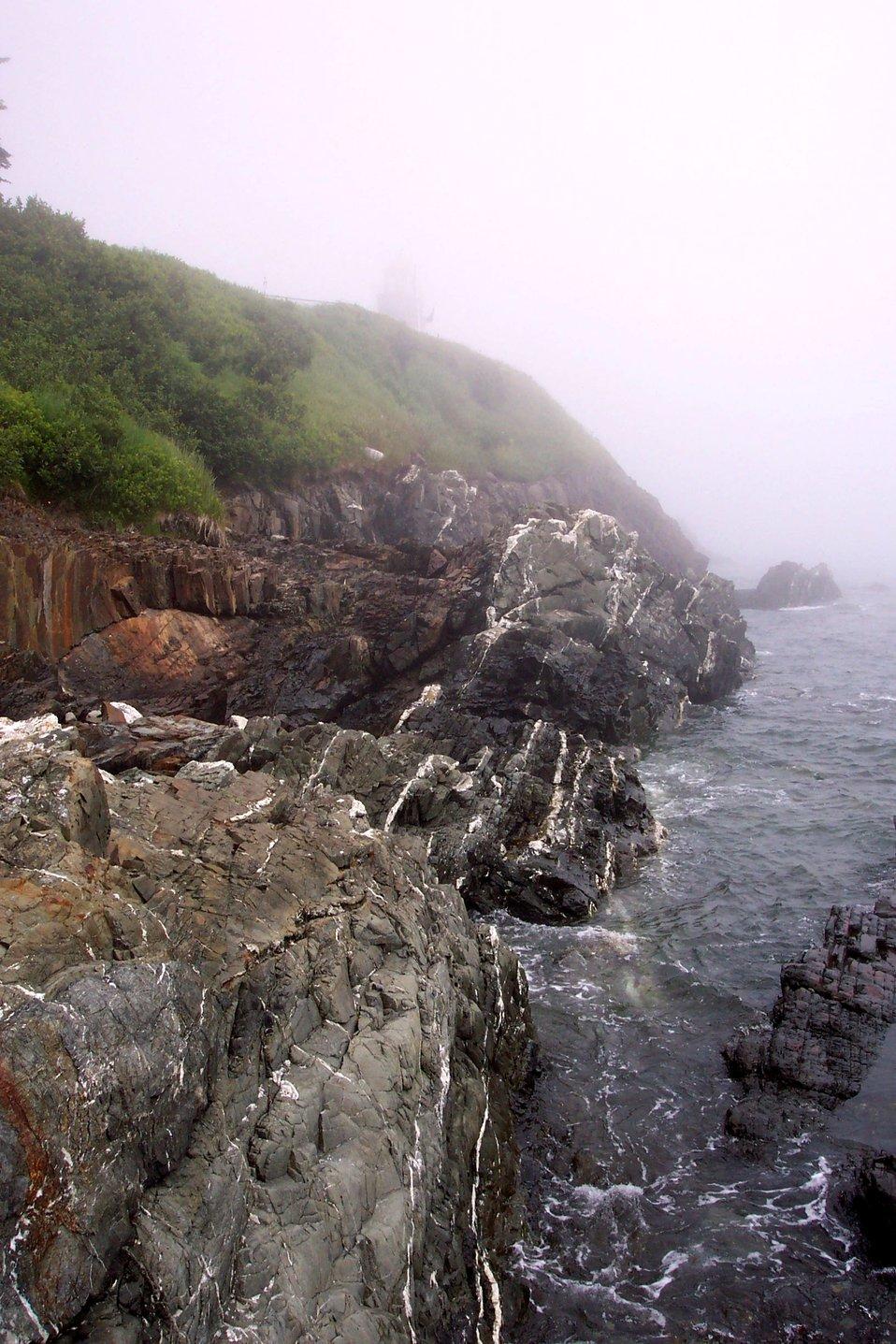 Quartz-veined metamorphic rocks meet the sea below a fog-shrouded lighthouse at West Quoddy Head.