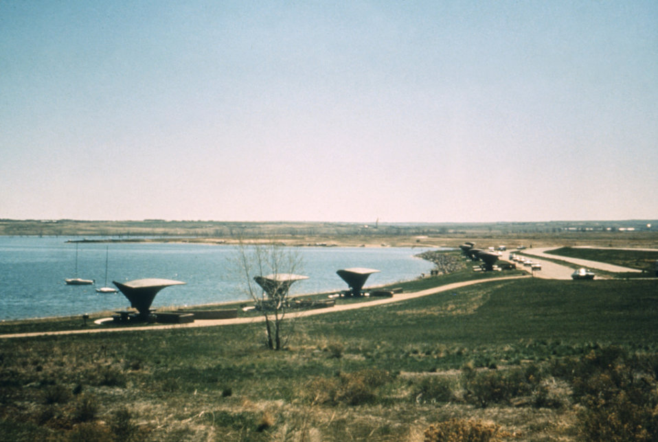 This 1976 photograph shows a number of picnic shelters along a lake shore in Colorado.