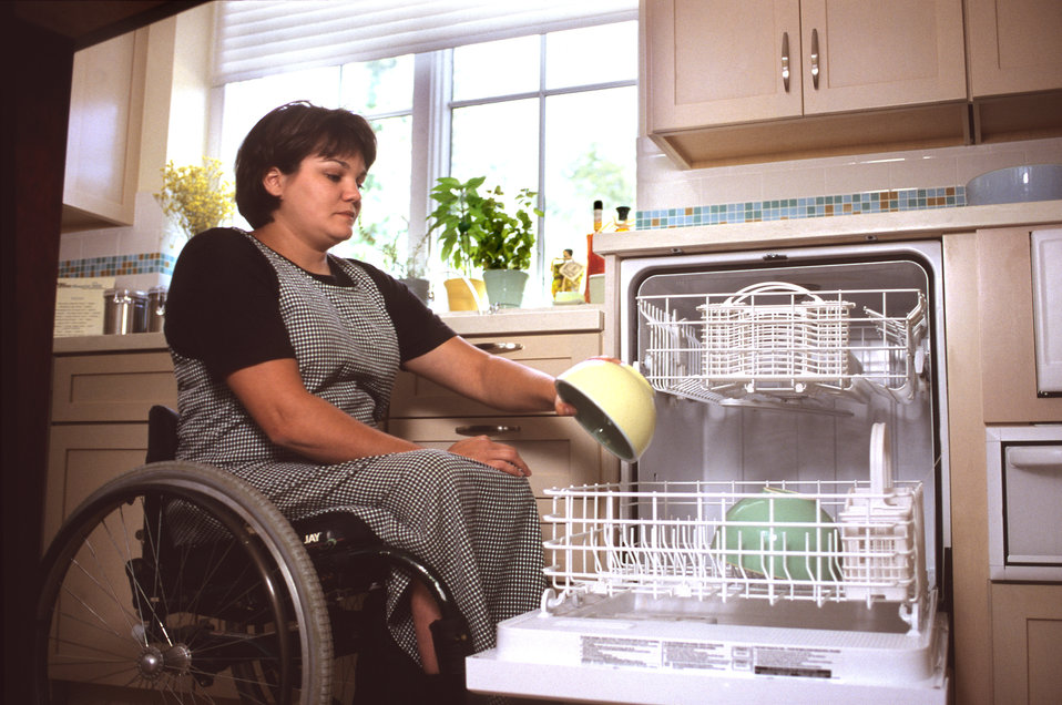This 2000 image depicted a universally-designed, raised dishwasher that was being loaded by a wheelchair-seated woman, who seemed to be fill