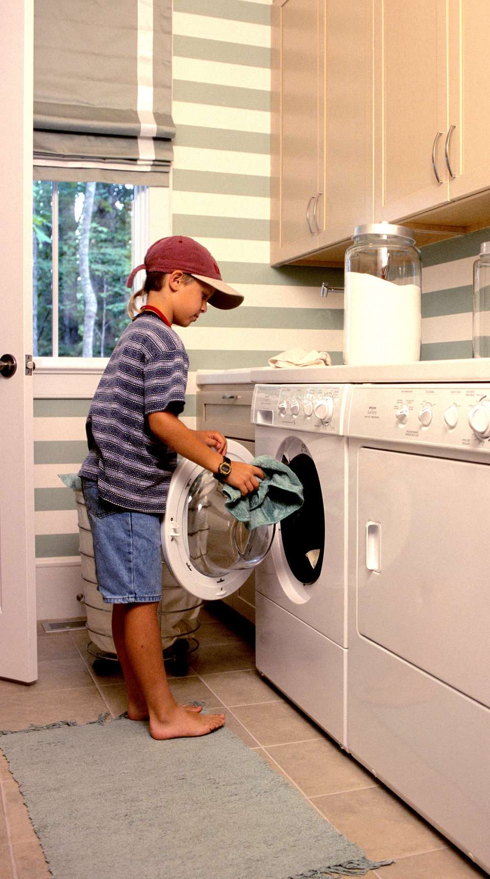This 2000 image showed a young boy utilizing a front-loading clothes washing machine, which was located directly adjacent to a front-loading