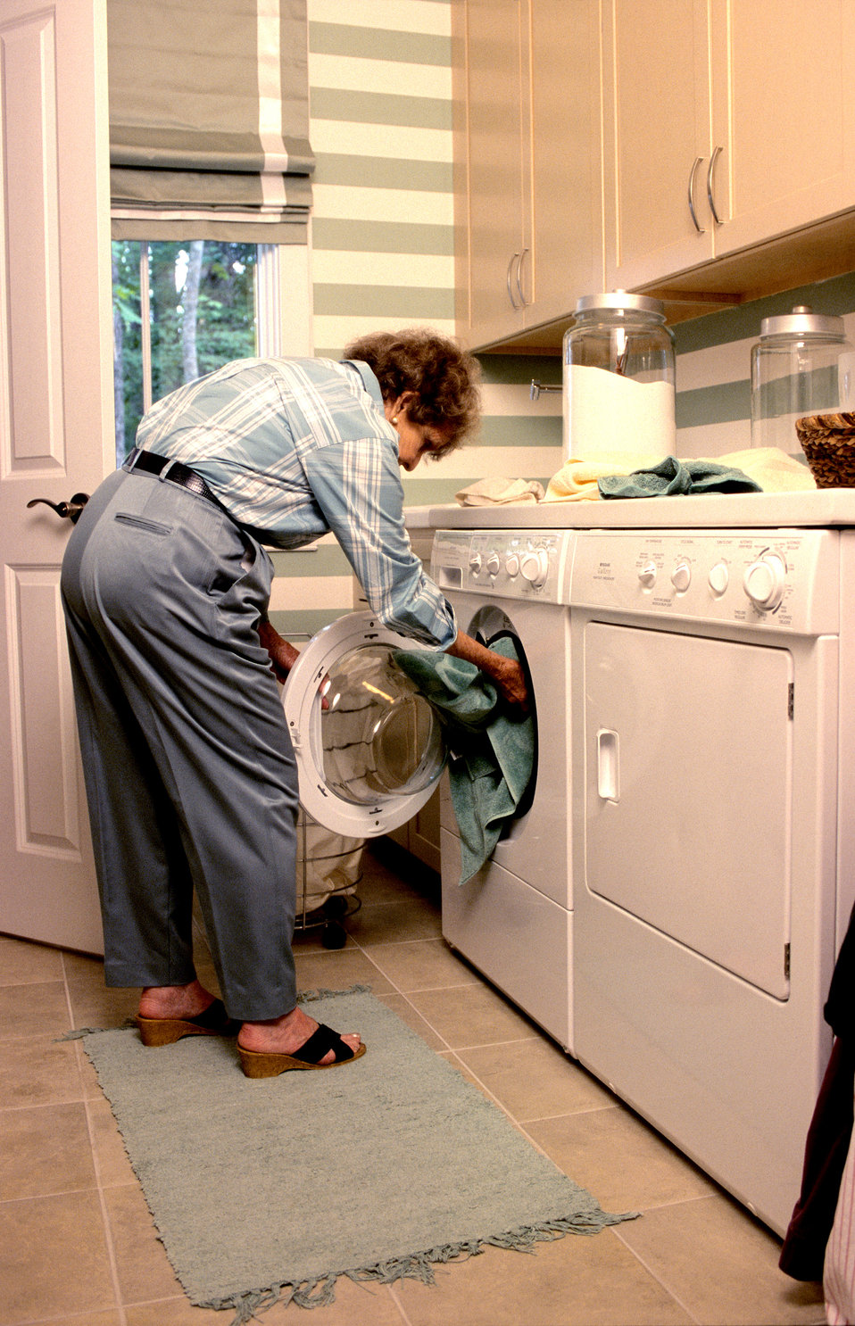 This 2000 image depicted an elderly woman filling a front-loading clothes washing machine, which was located directly adjacent to a front-lo