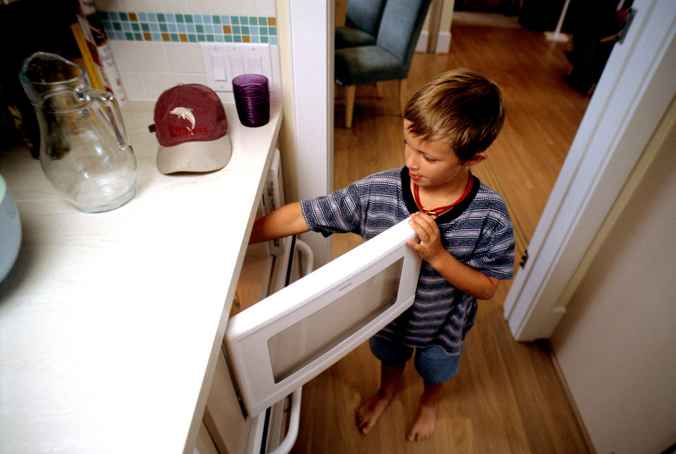This was one of two images (see PHIL 9386), showing a young boy who was using a microwave oven that had been installed beneath a kitchen cou