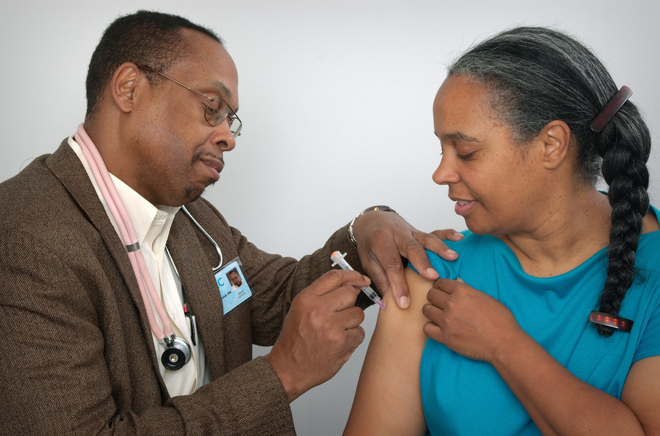 In this image, a qualified healthcare practitioner was in the process of administering an intramuscular immunization to a woman, using the w
