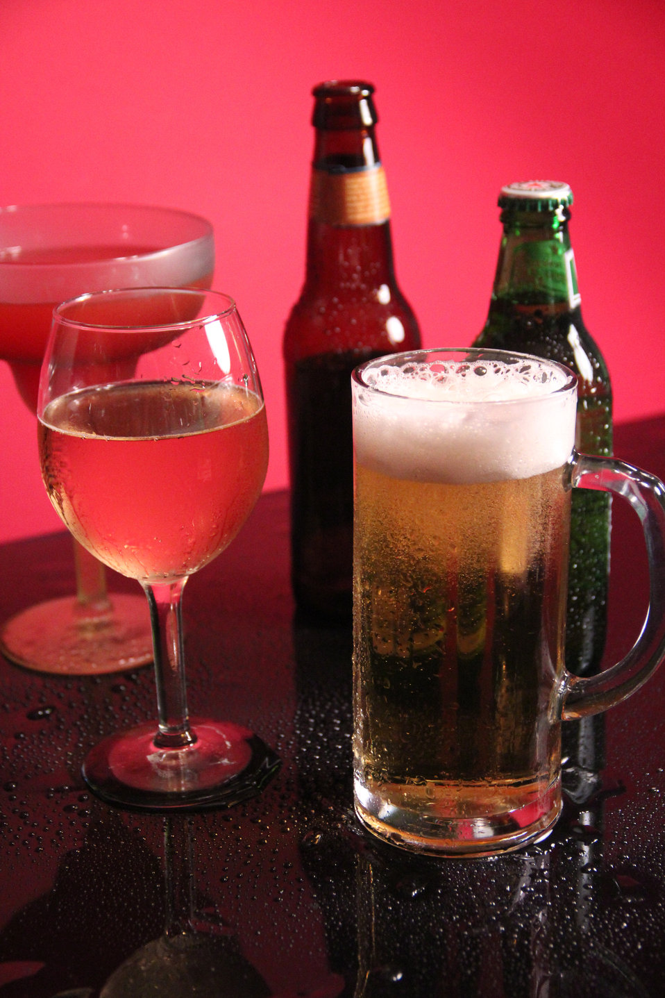 This image depicts a mixed drink and beer still life, which included one unopened, and one opened bottle of beer, a mug of freshly poured be