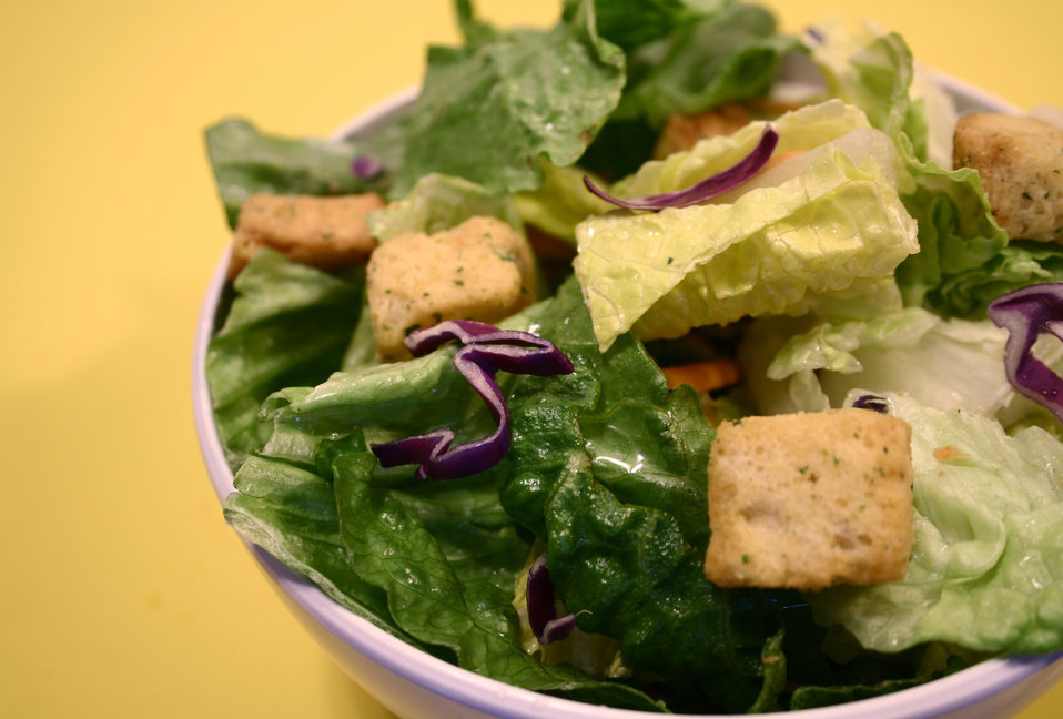 This photograph depicts a white ceramic bowl, which had been filled with a variety of lettuce leaves, croutons, and a salad dressing. The bo
