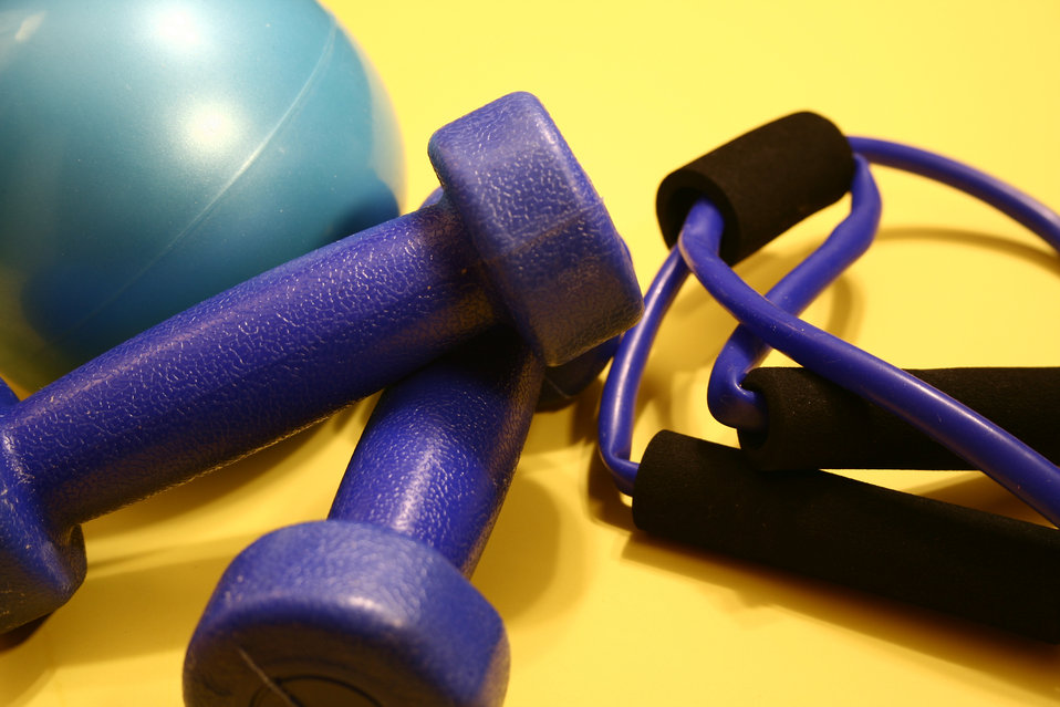 This image depicts a still life composed of exercise equipment including a turquoise rubber ball, a pair of light-weight dumbbells, and an e
