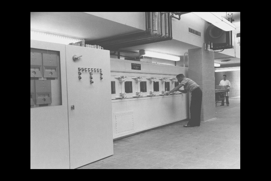 Employee adjusting controls on a Woodman Machine (glassware washer) at the Centers for Disease Control (CDC).