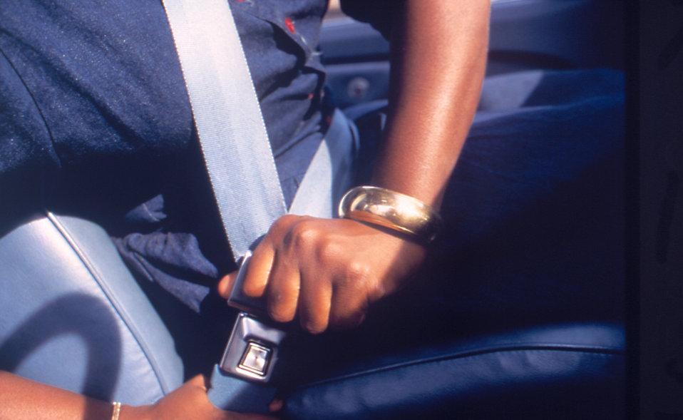 Person fastening seat belt in motor vehicle.