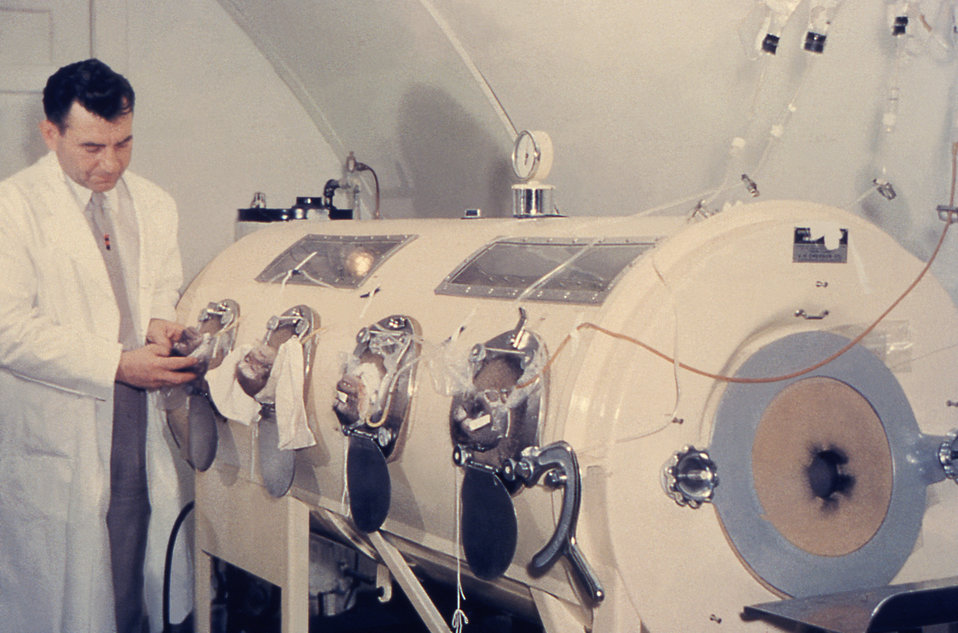 This historic photograph shows a technician calibrating an iron lung machine.