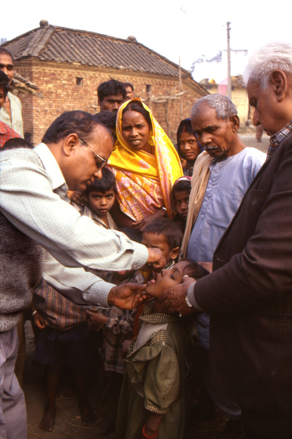 This 2000 photograph depicted a local Indian public health care practitioner administering an oral polio vaccine dosage to a child in an out
