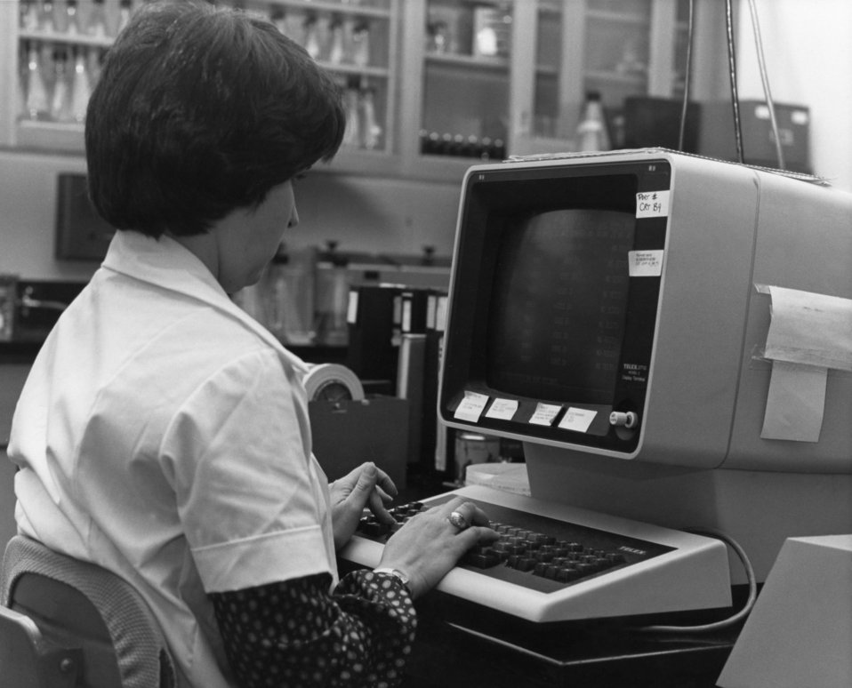 This 1980's photograph, taken within a Centers for Disease Control influenza testing laboratory, showed a laboratorian entering data into an