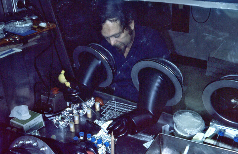 This photograph showed CDC virologist Karl M. Johnson, M.D., working with specimens through the sealed portals of a 'glove box' during a 197