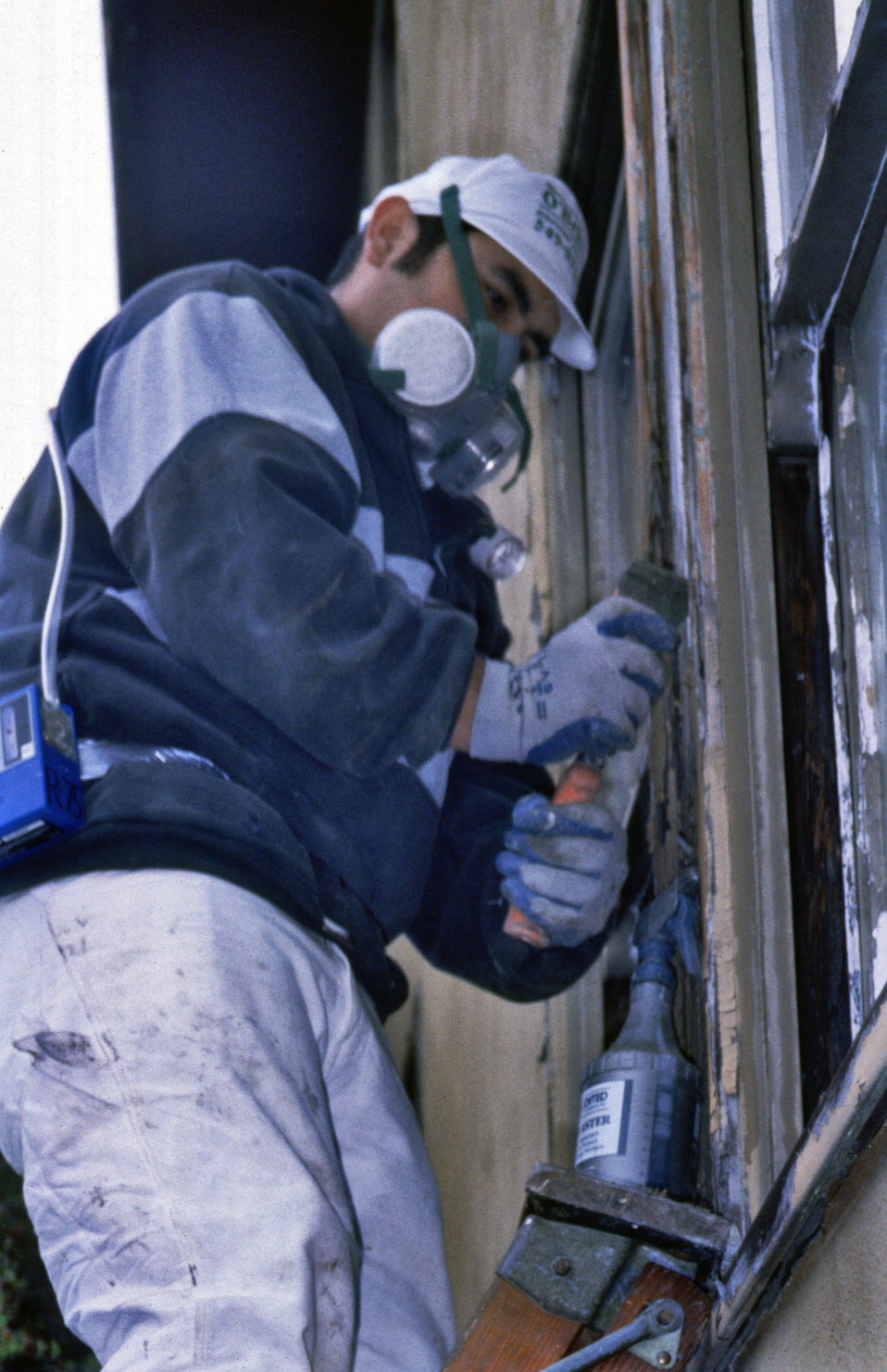 While wearing a protective mask, this worker was performing wet manual paint scraping in a 1999 exercise, demonstrating an exterior renovati