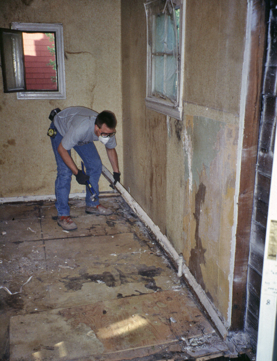 This 1993 photograph shows a worker removing a wood baseboard covered with lead-based paint, demonstrating renovation methods typically used